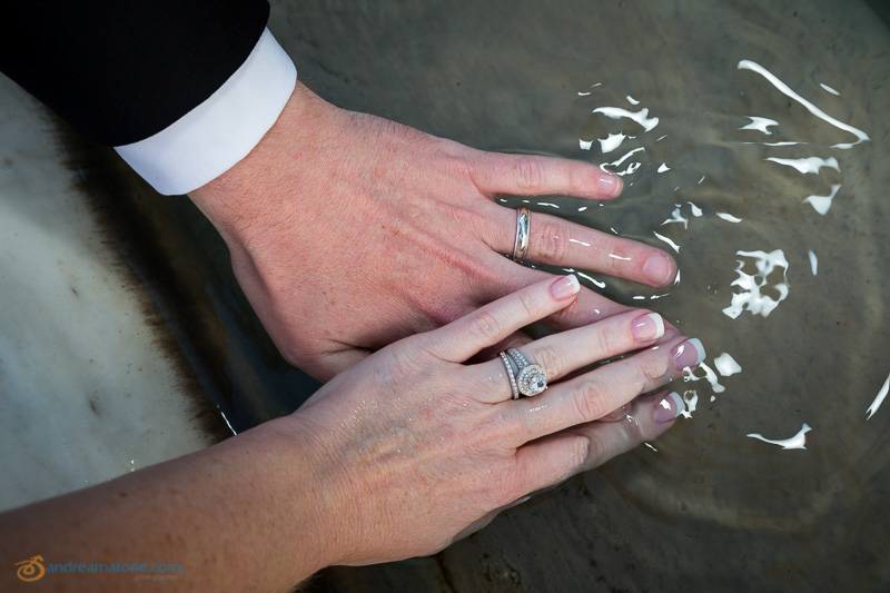 The hands of the newlyweds in the water.