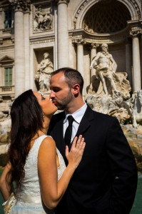 Newlyweds kissing at the Trevi fountain in Rome Italy.