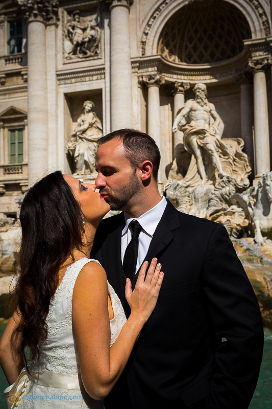 Newlyweds kissing at the Trevi fountain. Rome Destination Wedding Photographer.