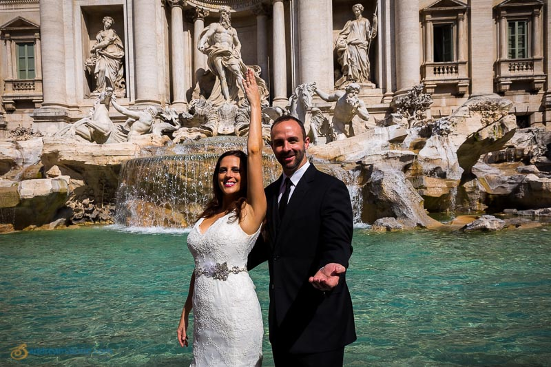Wedding couple throwing the coin into the water fountain at Piazza Fontana di Trevi.