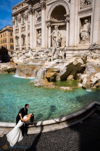 Romantic wedding couple kissing at the Trevi fountain in Rome.