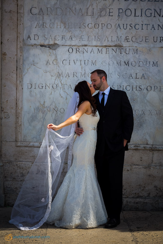 Kissing in front of an ancient marble slab.