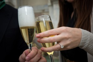 Close up picture of hands holding champagne glasses with the ring showing