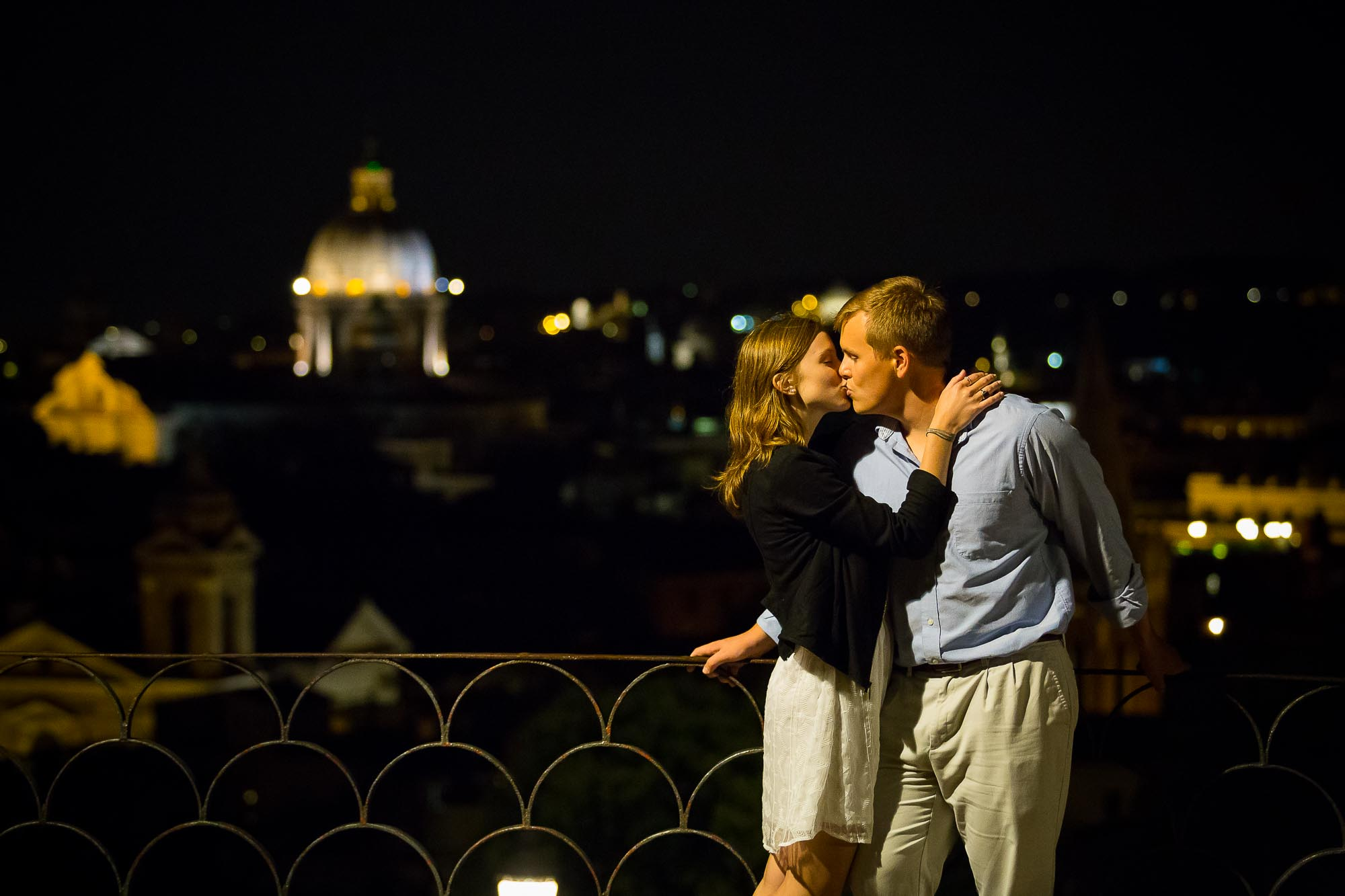 Kissing in love before the roman rooftops at night.