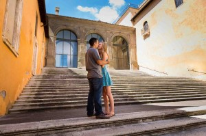 Engaged couple kissing on the steps of the Campidoglio Piazza