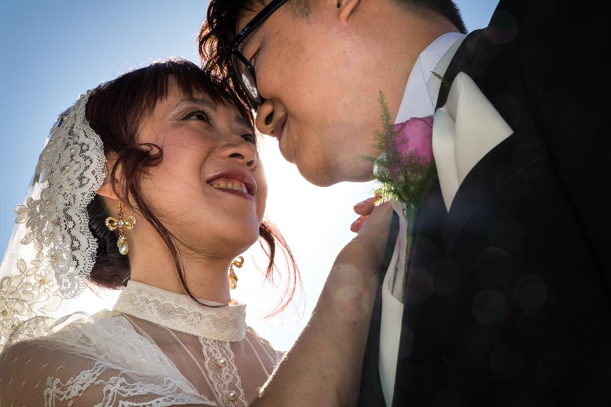 Close up photo of the newlyweds against blue sky