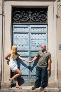 Couple just engaged holding hands in front of an interesting door.