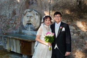 Portrait picture of bride and groom standing in front of a water fountain in the Aranci garden.