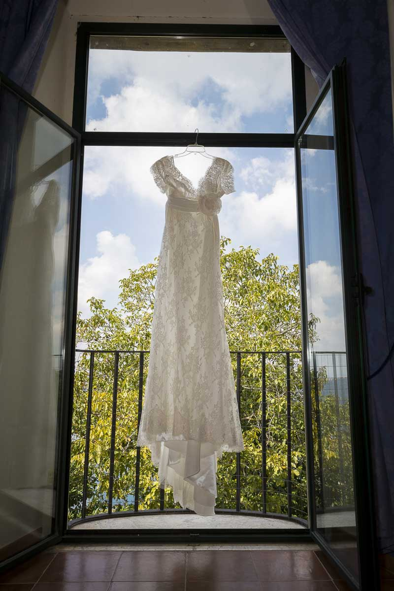 Wedding dress hanging from the window.