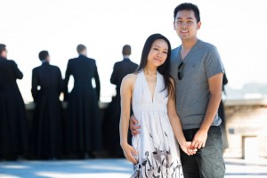 Couple portrait picture with out of focus priests in the background