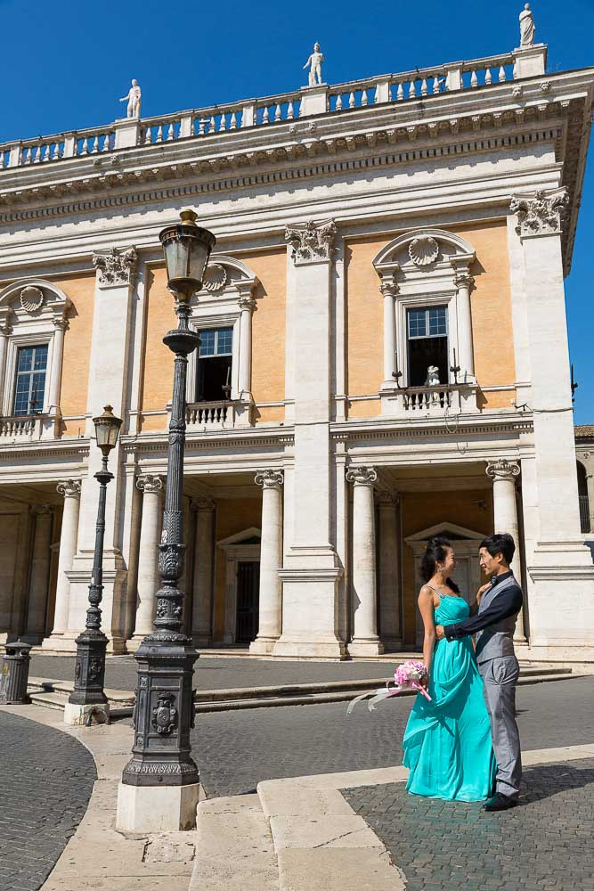 Couple photographed in Piazza del Campidoglio during a prewedding session. Building architecture.