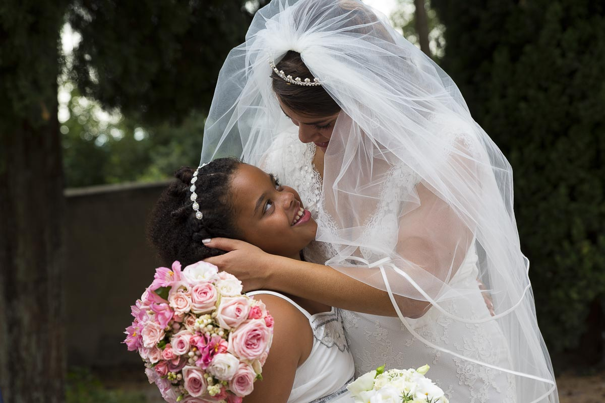Bride with a flower girl. Touching moment.