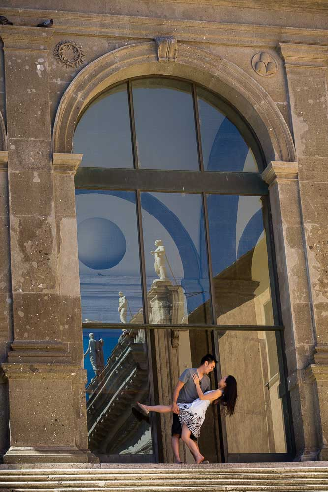 Photography of man and woman posing on top of the stairs found in Piazza del Campidoglio.