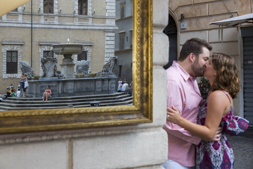 Engaged couple reflected in a mirror at Piazza Trastevere in Rome Italy.