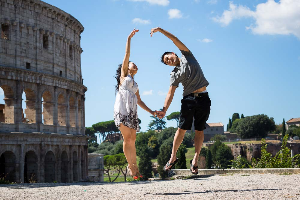 Making a heart shaped by jumping at the Roman Colosseum in Rome.