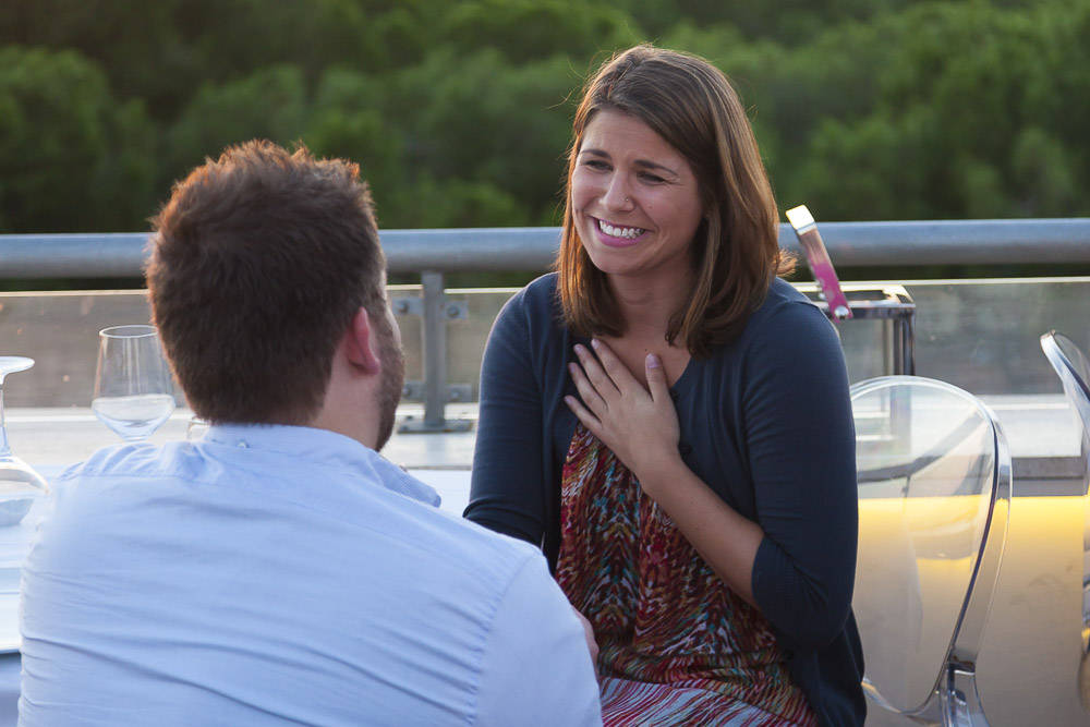 Joyful reaction to a wedding proposal question asked on top of a restaurant. Engagement Proposal Photography.