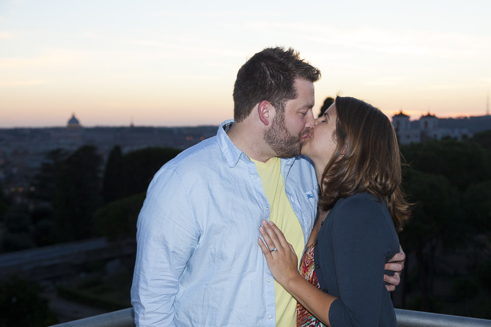 Couple kissing on top of a restaurant with a stunning view over the rooftops.