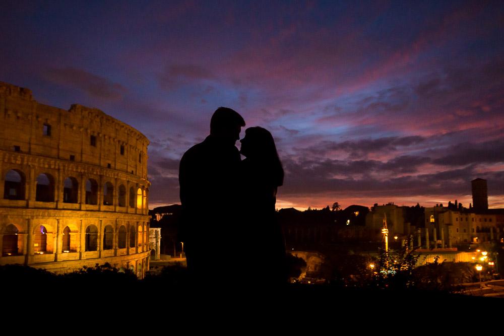Silhouette figures in the dark in front of the Coliseum