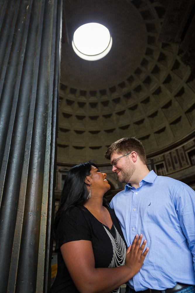 A couple standing at the entrance of the Pantheon with the hole light above.