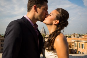 Couple kissing during a photo shoot overlooking the roman rooftops at Trinita' dei Monti.