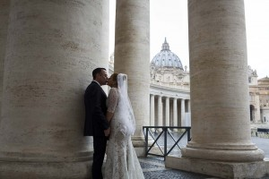 Kissing in Saint Peter's square with the Saint Peter's Basilica in the far distance. Wedding in Rome, Italy.
