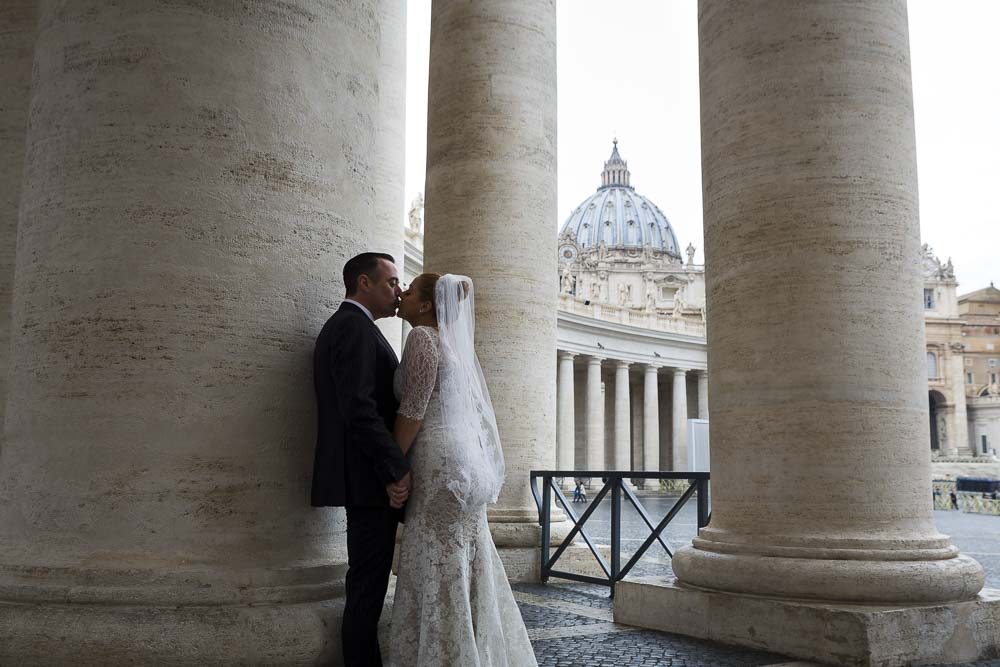 Kissing in Saint Peter's square with the Basilica dome in the far distance. Wedding Blessing Photography in Rome, Italy.