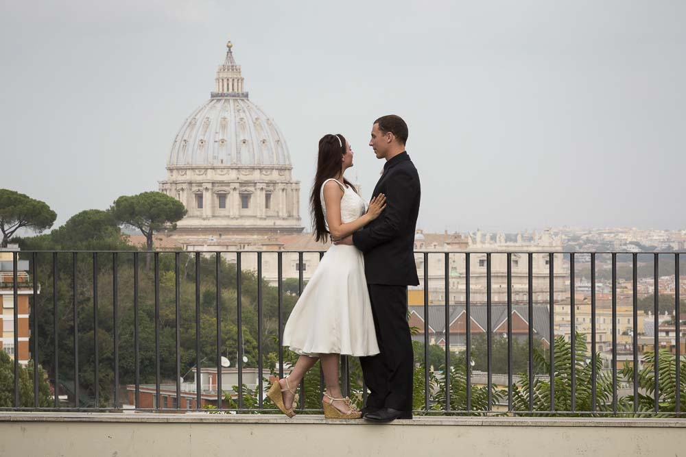 Couple on their honeymoon in Rome overlooking the roman Vatican dome.