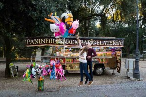 Couple jumping up in the air trying to catch some balloons in front of a gelato stand.
