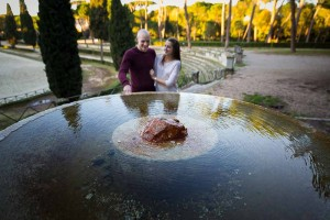 Couple portrait picture around a circular water fountain with the reflection.