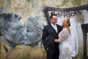 Wedding pictures taken down the tiber river with some graffiti in the background.