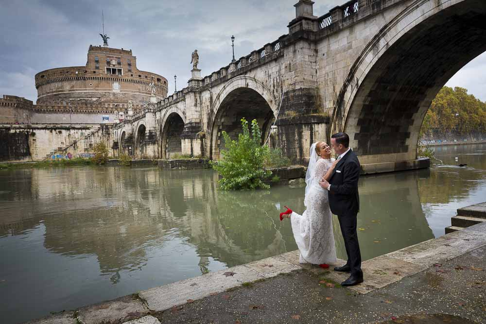 Bride and groom down underneath the bridge of Saint Angel Castle in Rome.