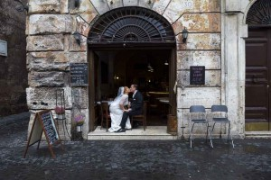 Bride and groom drinking a glass of red wine after their wedding blessing in Rome.