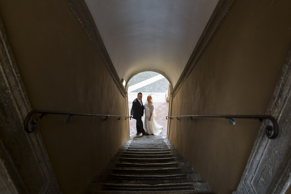 View of groom and bride inside a staircase tunnel.