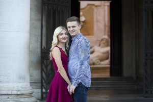 Portrait picture of a couple posing in front of old marble statues.