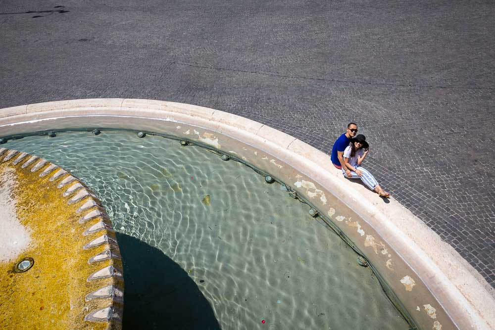 Engagement photo session in Rome by the Piazza del Popolo water fountain.