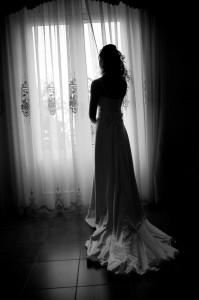 Bride looking at the window. Black and white picture.