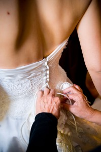 Bride preparation photography. The closing of the dress.