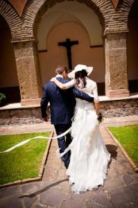 Italian catholic wedding. Bride and groom walk towards the Church.