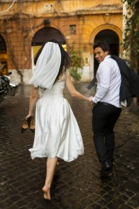 Bride and groom running under rain during their wedding day
