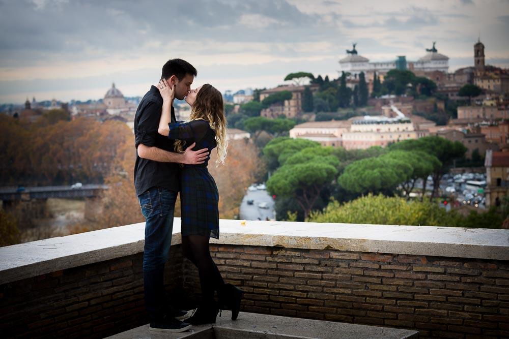 Kissing overlooking the roman skyline from the Giardino degli Aranci park