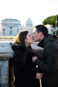 A couple kiss on the bridge of Castel Sant Angelo overlooking the Vatican city in the distance