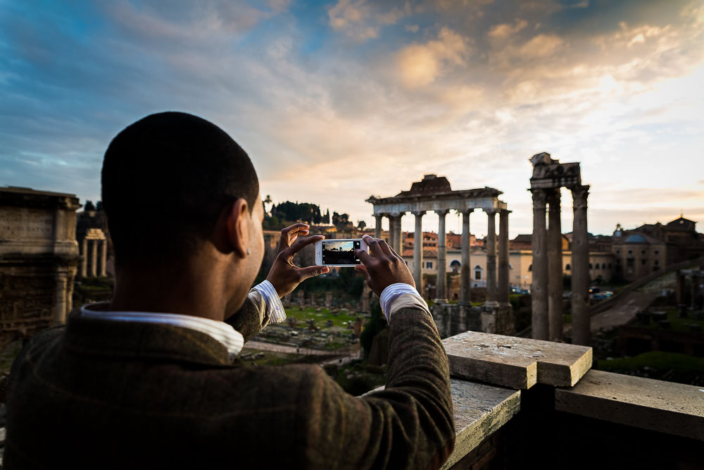 Man taking a picture of the roman forum at sunset
