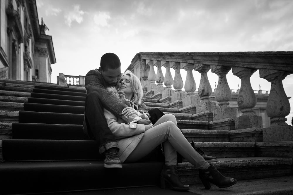 Black & white picture of a couple in love in Rome. Sitting down on steps.