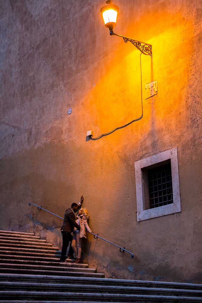 Romantic picture of a couple under roman street light. Romance in Italy.