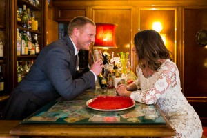 Playful image of a couple about to get married taking pictures at a Hotel bar