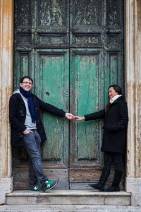 Portrait image of an engaged couple in front of a worn down green door
