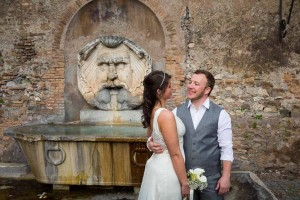 Newlyweds outside Giardino Aranci park in front of a water fountain