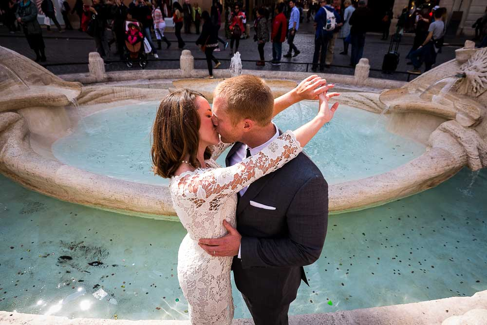 Couple in love in Rome after a wedding celebration. Photographed by the Barcaccia water fountain.