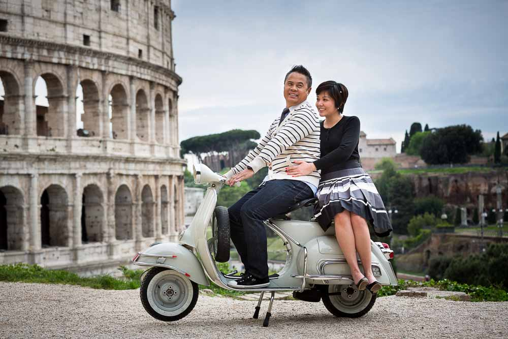 Couple sitting down on an antique Vespa moped during their wedding engagement shoot in Rome