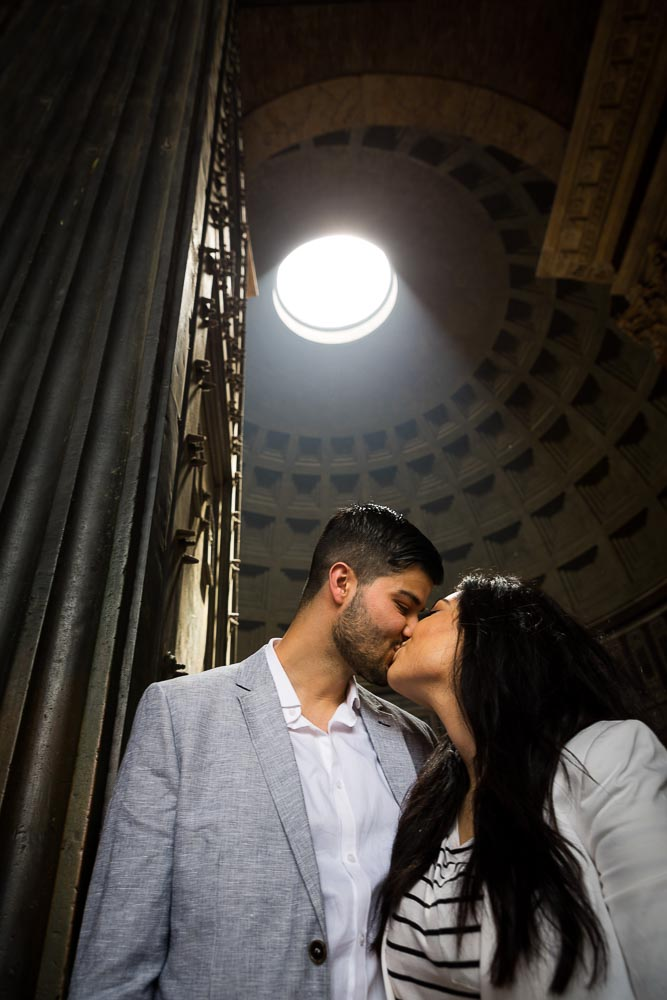 Engagement session in Rome. Kissing underneath the light from the Roman Pantheon hole